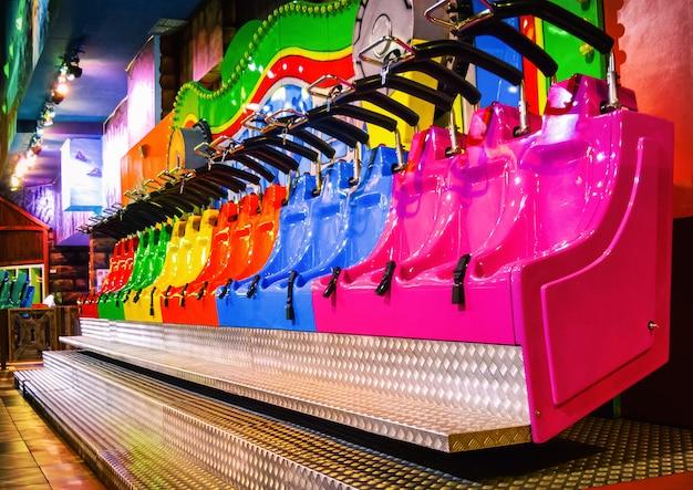 Asientos de montaña rusa de colores en el parque de atracciones