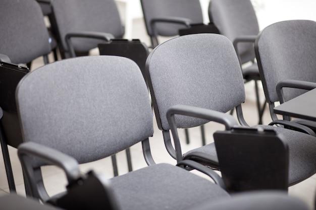 Asientos de silla gris en una sala de conferencias vacía.