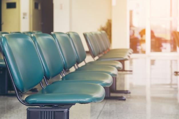 Los asientos vacíos en un negocio o las sillas son de cuero verde con patas de metal y sin reposabrazos.
