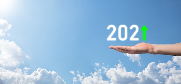 Asimiento de la mano 2021 icono positivo en el fondo del cielo.planifique el crecimiento positivo del negocio en el concepto del año 2021. plan de empresario y aumento de indicadores positivos en su negocio, conceptos de negocio creciendo.