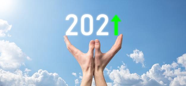 Asimiento de la mano 2021 icono positivo sobre fondo de cielo.planifique el crecimiento positivo del negocio en el concepto del año 2021 plan de empresario y aumento de indicadores positivos en su negocio, conceptos de negocio creciendo.