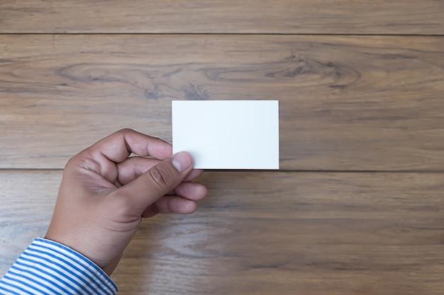 Asimiento de la mano en blanco tarjeta blanca maqueta negocio de marca
