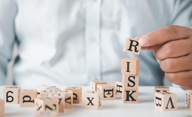 Asimiento de la mano bloque de madera con la palabra riesgo