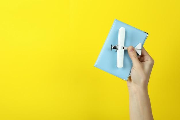 Asimiento de la mano femenina avión de juguete y pasaporte sobre fondo amarillo