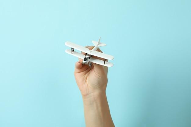 Asimiento de la mano femenina avión de juguete sobre fondo azul.