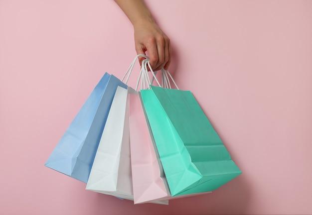Asimiento de la mano femenina bolsas de papel sobre fondo rosa