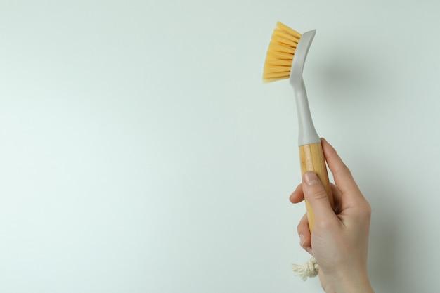 Asimiento de la mano femenina cepillo ecológico sobre fondo blanco.