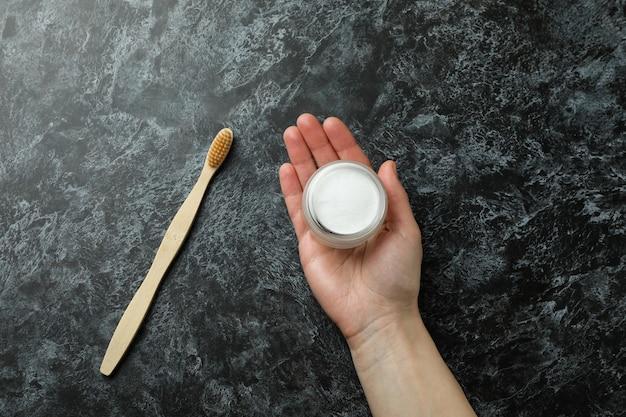 Asimiento de la mano femenina polvo de dientes sobre fondo negro ahumado con cepillo de dientes