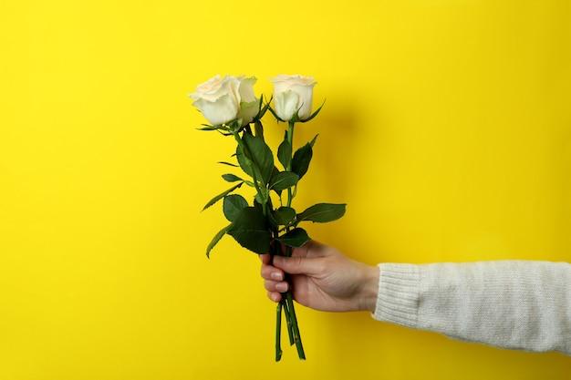 Asimiento de la mano femenina rosas en amarillo