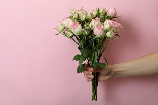 Asimiento de la mano femenina rosas en rosa