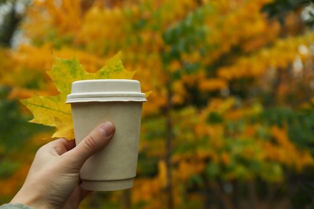 Asimiento de la mano femenina taza de papel en el fondo del parque otoño