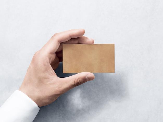 Asimiento de la mano maqueta de diseño de tarjeta de visita kraft simple en blanco