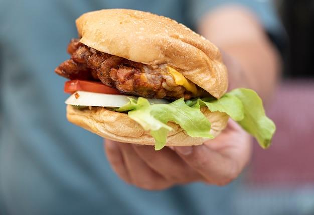 Asimiento de la mano las mejores hamburguesas de sándwiches de pollo frito de comida rápida
