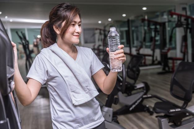 Asimiento de la mano de la muchacha asiática botella de agua potable en el club deportivo fitness y sonriente