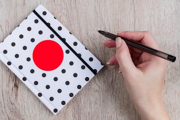 Asimiento de la mano de mujer joven lápiz negro y cuaderno de lunares en mesa de madera