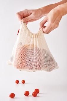 Asimiento de la mano de mujer vegetales orgánicos frescos en bolsa textil, cero residuos y concepto de compra