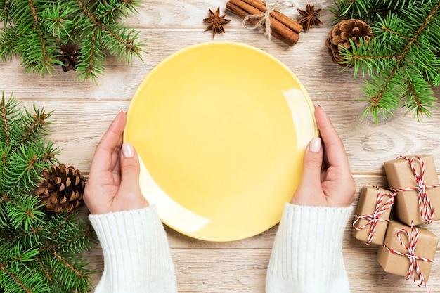 Asimiento de la mano de niña placa amarilla vacía con decoración de navidad. vista superior del concepto de año nuevo