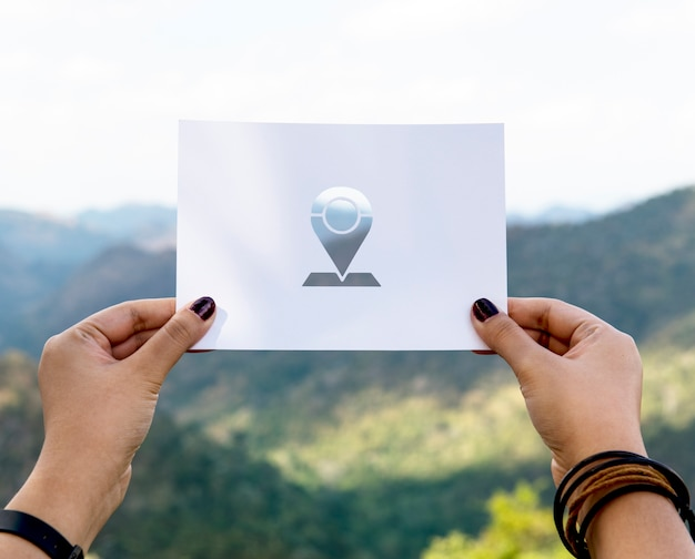 Asimiento de la mano pin etiqueta de papel tallado con fondo de montaña