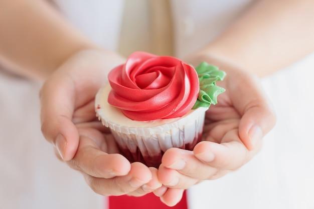 Asimiento de la mano de san valentín cupcake rosa roja