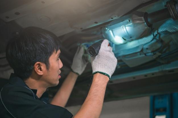 Asimiento mecánico masculino asiático y linterna brillante para examinar el automóvil debajo del chasis