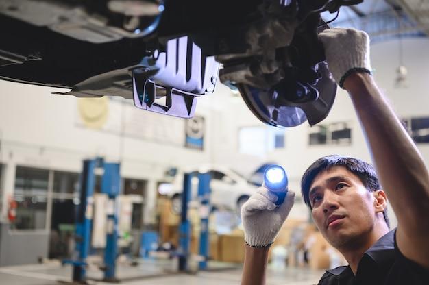 Asimiento mecánico masculino asiático y linterna brillante para examinar la pastilla de freno de disco del automóvil