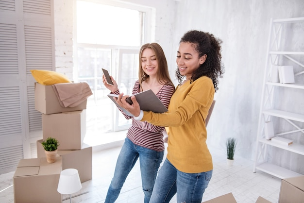 Asistencia con la mudanza. chicas alegres y agradables que revisan el cuaderno en busca de una empresa de mudanzas antes de mudarse del dormitorio.