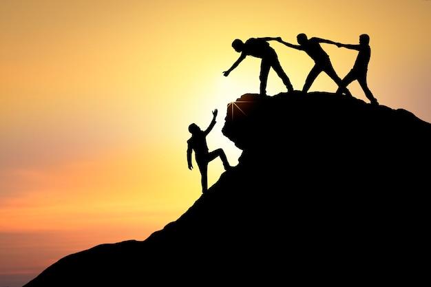 Asistencia, trabajo en equipo y concepto de logro. silueta del hombre que ayuda al amigo al éxito
