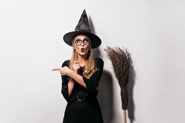 Asistente asombrado en vasos de pie sobre una pared blanca. bruja emocional divertida posando con sombrero y escoba.