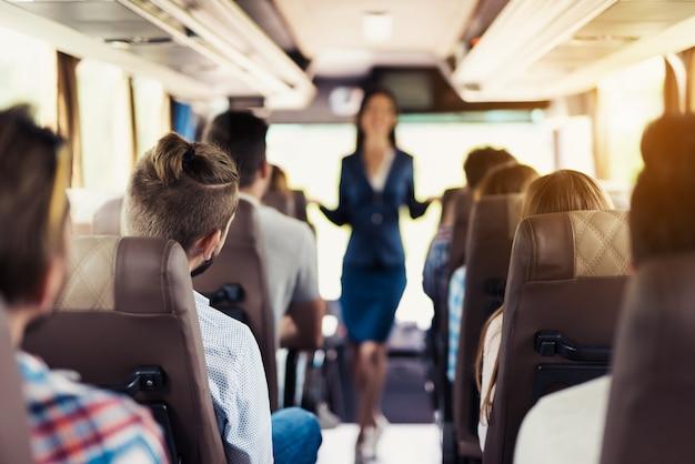 Asistente de autobús en uniforme y pasajeros felices.