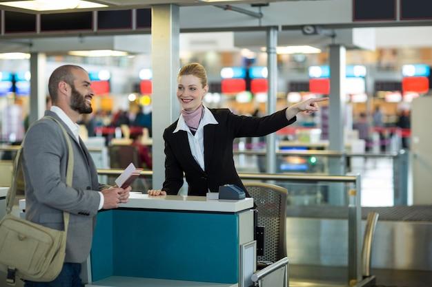 Asistente de check-in de la aerolínea que muestra la dirección al viajero en el mostrador de check-in