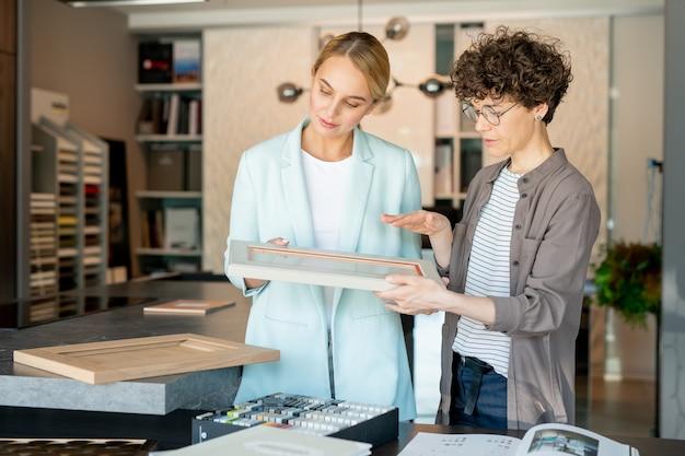 Asistente de confianza joven de la tienda de regalos que ofrece marco de imagen a uno de los clientes