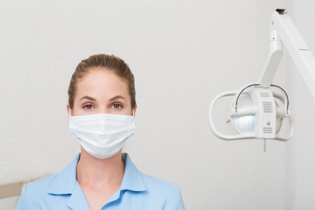 Asistente dental en máscara mirando a cámara