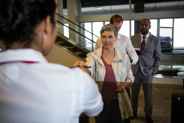 El asistente de facturación de la aerolínea entrega el pasaporte al pasajero