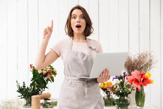 Asistente feliz mujer vistiendo delantal apuntando con el dedo hacia arriba y sosteniendo el portátil, mientras trabaja en la tienda de flores