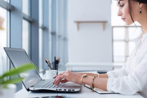 Asistente femenina trabajando, escribiendo, usando una computadora portátil, concentrada, mirando el monitor. trabajador de oficina leyendo correo electrónico empresarial.