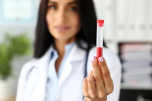 Asistente femenino mostrando en cámara tubo de ensayo de plástico