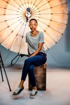 Asistente de fotógrafo posando delante de un paraguas reflectante en un estudio