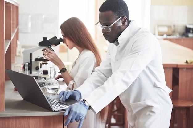 Asistente de laboratorio con bulbo de cristalería de laboratorio microscopio con productos químicos.