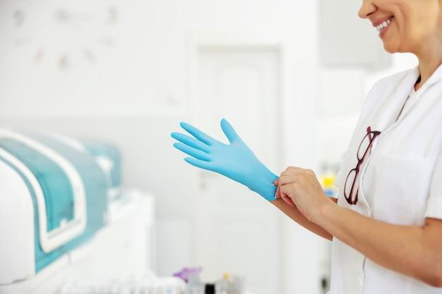 Asistente de laboratorio femenino en abrigo poniéndose guantes de goma mientras está de pie en el laboratorio.