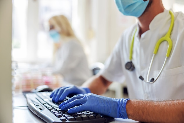 Asistente de laboratorio masculino sentado en el laboratorio e ingresando datos en la computadora durante el brote del virus corona.