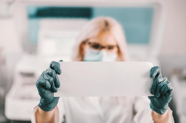 Asistente de laboratorio de pie en el laboratorio y sosteniendo papel con resultados. concepto de brote de virus corona.