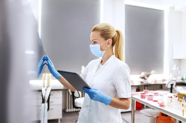 Asistente de laboratorio sosteniendo la tableta y usando la computadora para ingresar los resultados de la prueba durante el virus corona.