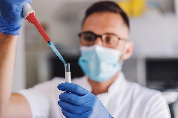 Asistente de laboratorio sosteniendo un tubo de ensayo con sangre e investigando la cura del coronavirus.