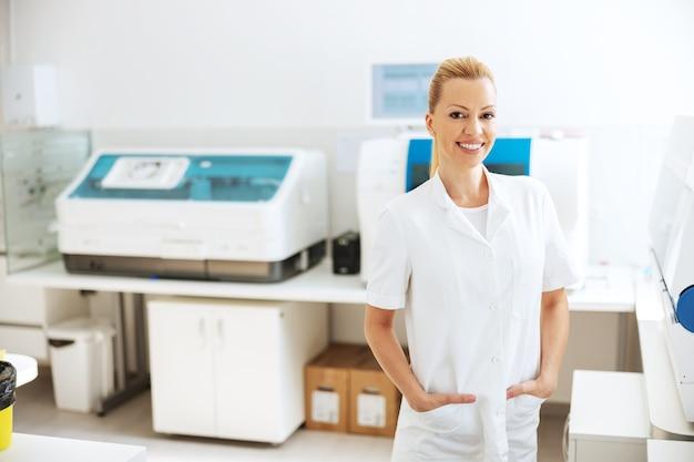Asistente de laboratorio en uniforme blanco estéril de pie en laboratorio con las manos en los bolsillos.