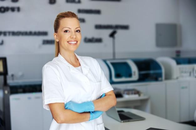 Asistente de laboratorio en uniforme estéril con guantes de goma de pie en laboratorio con los brazos cruzados.