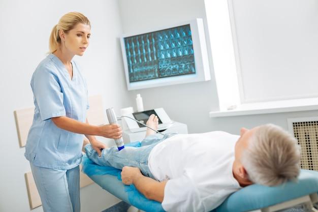 Asistente médico. agradable agradable mujer hábil de pie cerca del paciente y usando un dispositivo de ultrasonido mientras realiza un chequeo médico