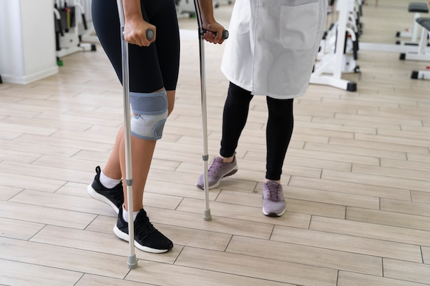 Asistente médico ayudando al paciente con ejercicios de fisioterapia