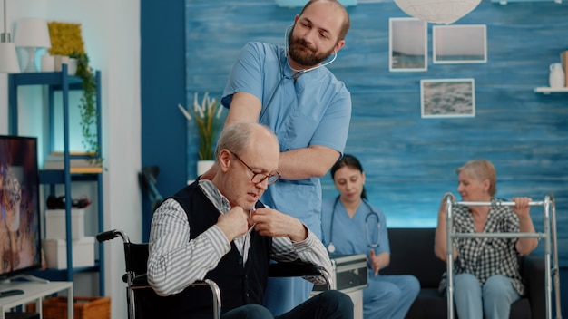 Asistente médico consulta hombre discapacitado con estetoscopio