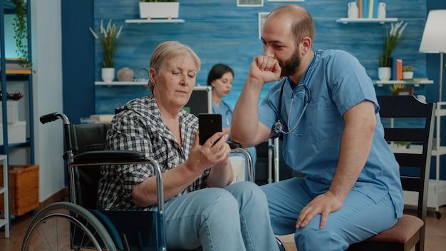 Asistente médico enseñando a anciana discapacitada a usar el teléfono inteligente