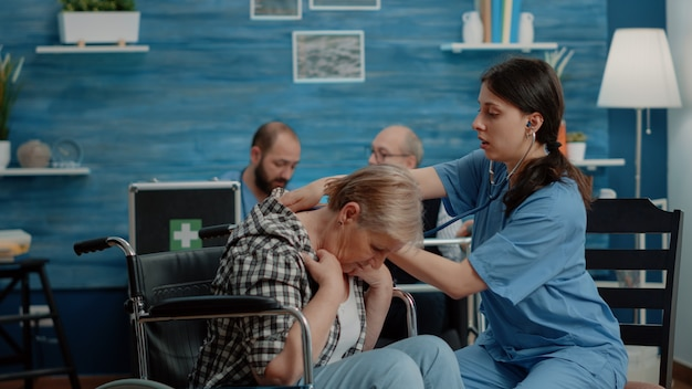 Asistente médico con estetoscopio en paciente senior